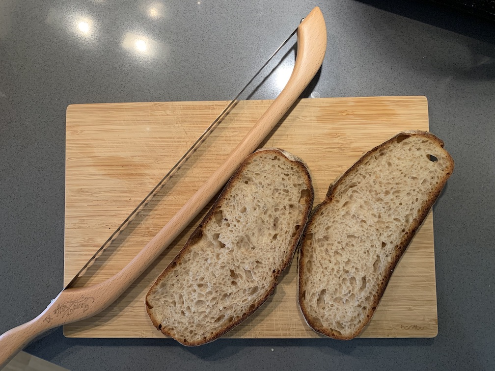 A weird bread knife with some slices of bread